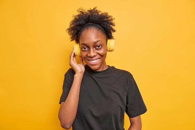 Portret van mooie dunne afro-amerikaanse vrouw luistert naar muziek via een draadloze koptelefoon