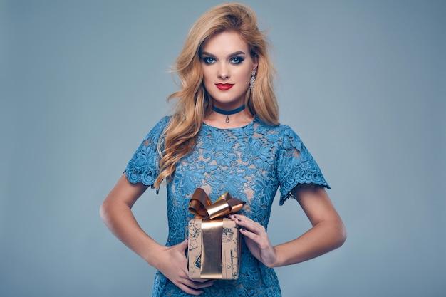 Portret van mooie elegante vrouw in modieuze kleding met cadeau