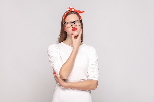 Portret van mooie emotionele jonge vrouw in wit t-shirt met sproeten, zwarte bril, rode lippen en hoofdband die haar kin aanraakt en denkt. indoor studio opname, geïsoleerd op lichtgrijze achtergrond.