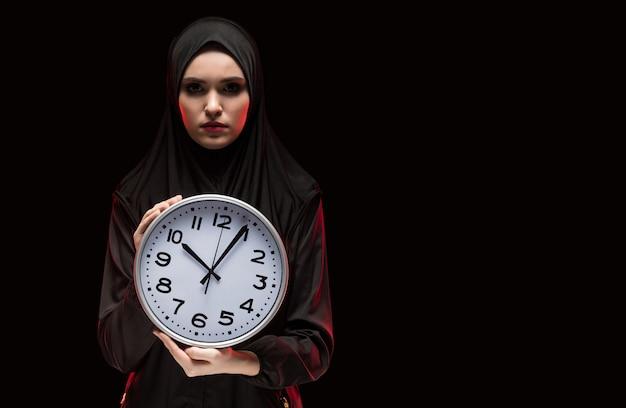 Portret van mooie ernstige bang bange jonge moslimvrouw die zwarte hijab holdingsklok in haar handen draagt als tijd die concept op zwarte achtergrond opraakt