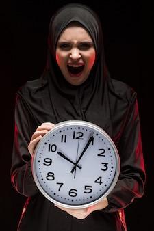 Portret van mooie ernstige doen schrikken bang gemaakte jonge moslimvrouw die zwarte hijab holdingsklok dragen