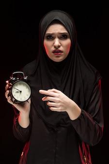 Portret van mooie ernstige doen schrikken bang gemaakte jonge moslimvrouw die zwarte hijab holdingswekker op zwarte achtergrond dragen