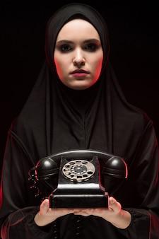 Portret van mooie ernstige doen schrikken jonge moslimvrouw die zwarte hijab aanbieden die telefoon als keusconcept roepen te roepen