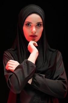Portret van mooie ernstige jonge moslimvrouw die zwarte hijab dragen als conservatief manierconcept met hand dichtbij haar gezicht op zwarte