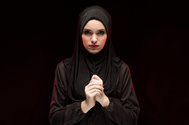 Portret van mooie ernstige jonge moslimvrouw die zwarte hijab met hand op hand dragen als het bidden concept op zwarte achtergrond