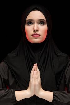 Portret van mooie ernstige jonge moslimvrouw die zwarte hijab met handen dragen dichtbij haar gezicht als het bidden concept