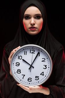 Portret van mooie ernstige moslimvrouw die zwarte hijab holdingsklok in haar handen draagt