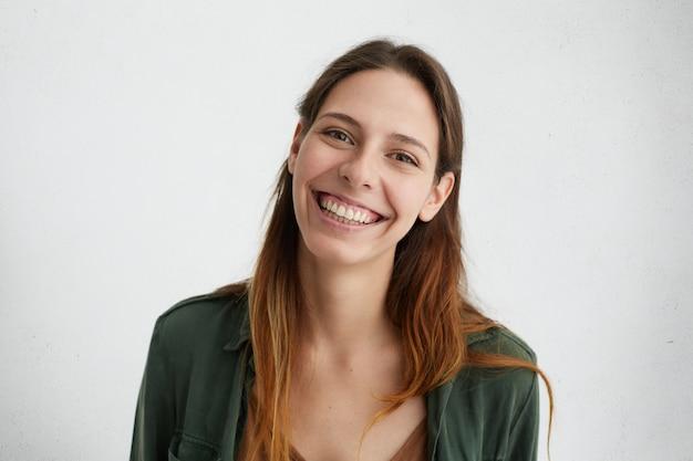 Portret van mooie europese vrouw met donker lang haar, gekleed in casual groen jasje glimlachend in grote lijnen haar witte perfecte tanden geïsoleerd. positieve vrouwelijke poseren