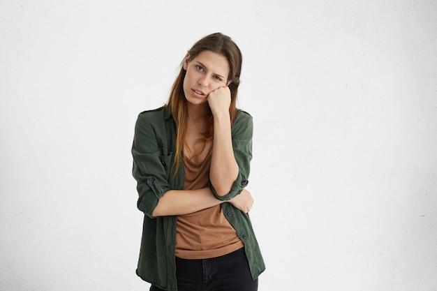Portret van mooie europese vrouw met lang haar gekleed in groen casual jasje op zoek uitgeput leunend naar haar hand
