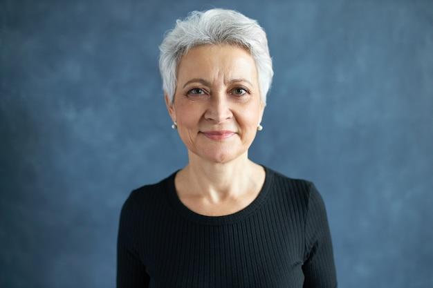 Portret van mooie europese vrouw van middelbare leeftijd met kort grijs haar en rimpels poseren geïsoleerd, gekleed in zwart t-shirt met vrolijke gelukkige gezichtsuitdrukking, glimlachen, in goed humeur zijn.