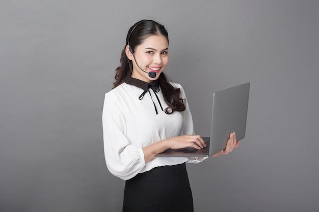 Portret van mooie exploitantvrouw op grijze achtergrond