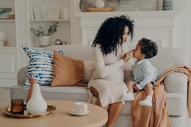 Portret van mooie familie zwangere moeder en zoon afro etnische race zittend op de bank