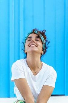 Portret van mooie gebruinde vrouw op vakantie. geïsoleerde vrouw op blauwe achtergrond. geluk concept