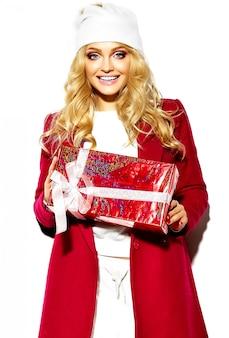 Portret van mooie gelukkig lieve lachende blonde vrouw meisje houdt in haar handen grote kerstcadeau doos in casual rode hipster winterkleren