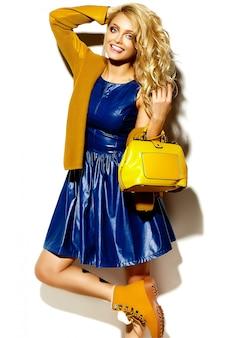 Portret van mooie gelukkig lieve lachende blonde vrouw vrouw in casual hipster warme winter trui kleding, met gele handtas