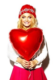 Portret van mooie gelukkig lieve schattige lachende blonde vrouw vrouw in casual hipster kleding, in roze rok en winter warme muts met rood hart ballon in handen