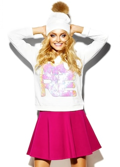 Portret van mooie gelukkig lieve schattige lachende blonde vrouw vrouw in casual hipster kleding, in roze rok en winter warme muts