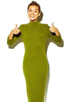 Portret van mooie gelukkig schattige lachende brunette vrouw meisje in casual groene hipster zomer kleding zonder make-up geïsoleerd op het tonen van duimen omhoog ondertekenen