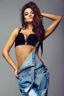 Portret van mooie gelukkig schattige lachende brunette vrouw slecht meisje in casual hipster denim overall kleding in zwarte lingerie