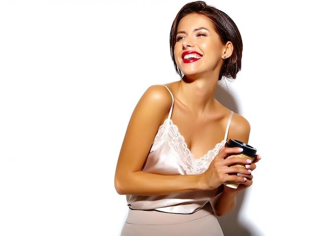 Portret van mooie gelukkig schattige sexy brunette vrouw met rode lippen in brede klassieke broek met plastic koffiekopje op witte achtergrond
