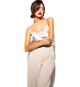 Portret van mooie gelukkig schattige sexy brunette vrouw met rode lippen in brede klassieke broek op witte achtergrond