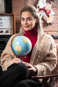 Portret van mooie gelukkige dame die een wereldbol houdt