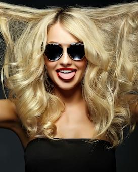 Portret van mooie gelukkige lieve schattige lachende blonde vrouw meisje met rode lippen en met krullend haar vliegende tonen haar tong
