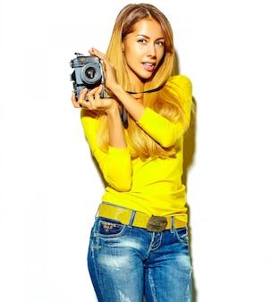 Portret van mooie gelukkige schattige lachende blonde vrouw meisje in casual zomerkleren neemt foto's met retro fotografische camera, geïsoleerd op een wit