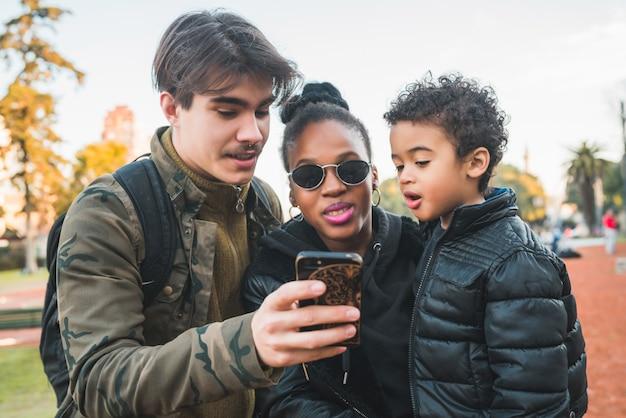 Portret van mooie gemengd ras etnische familie plezier, ontspannen en met behulp van mobiele telefoon in het park buiten.