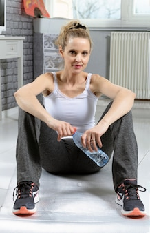 Portret van mooie geschiktheidsvrouw met fles water