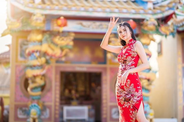 Portret van mooie glimlachende aziatische jonge vrouw die rode traditionele chinese cheongsam draagt, voor chinees nieuwjaarfestival bij chinees heiligdom