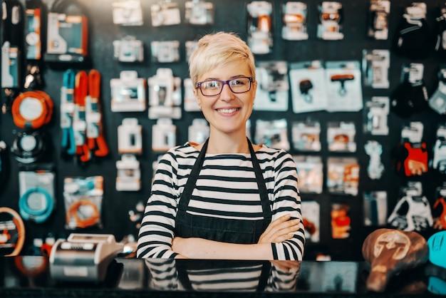Portret van mooie glimlachende blanke vrouwelijke werknemer met kort blond haar permanent in fietswinkel met gekruiste armen.