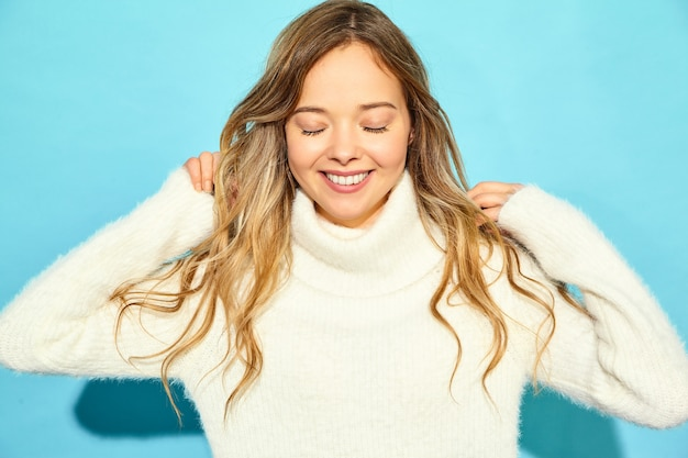Portret van mooie glimlachende blonde schitterende vrouw. vrouw die zich in modieuze witte sweater, op blauwe muur bevindt. concept van de winter