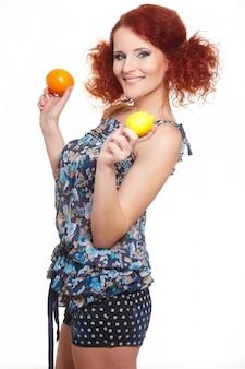 Portret van mooie glimlachende die roodharigegembervrouw in de zomerkleding op wit met sinaasappel en citroen wordt geïsoleerd