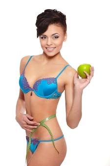 Portret van mooie glimlachende donkerbruine vrouw in witte lingerie met groene appel die perfecte die vorm meten op wit wordt geïsoleerd