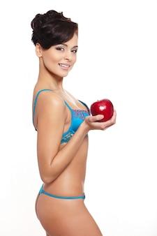 Portret van mooie glimlachende donkerbruine vrouw in witte lingerie met rood appeldieet dat op wit wordt geïsoleerd