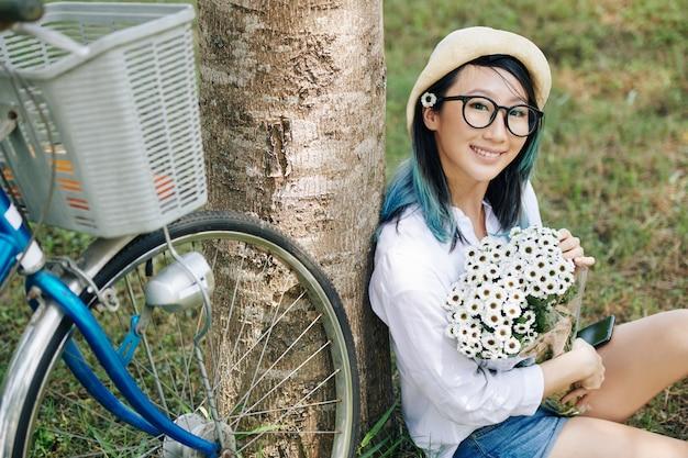 Portret van mooie glimlachende jonge chinese vrouw die met boeket van madeliefjes onder boom zit