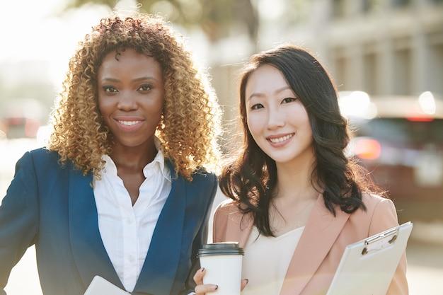 Portret van mooie glimlachende jonge vrouwelijke ondernemers die op een zonnige dag buiten staan, koffie drinken en naar de camera kijken