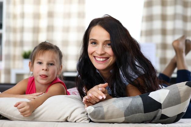 Portret van mooie glimlachende moeder die met dochtertje op bank in huiselijk interieur legt. mooi kind dat tong toont. het vreugdevolle kostbare concept van familiemomenten