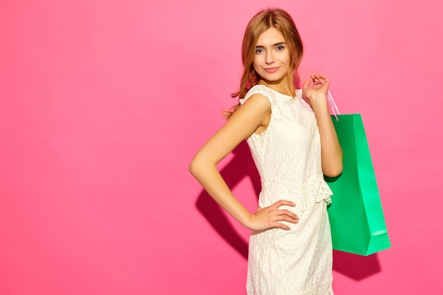 Portret van mooie glimlachende shopaholic vrouwen die kleurrijke document zakken houden. blonde vrouwen die op roze muur na het winkelen stellen. positief model