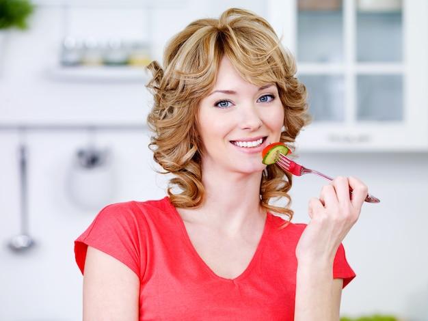 Portret van mooie glimlachende vrouw die de salade in de keuken eet