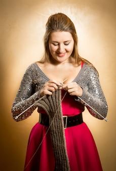 Portret van mooie glimlachende vrouw die lange sjaal breit