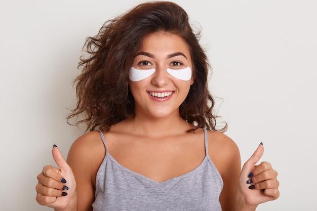 Portret van mooie glimlachende vrouw zonder make-up met patches undereyes