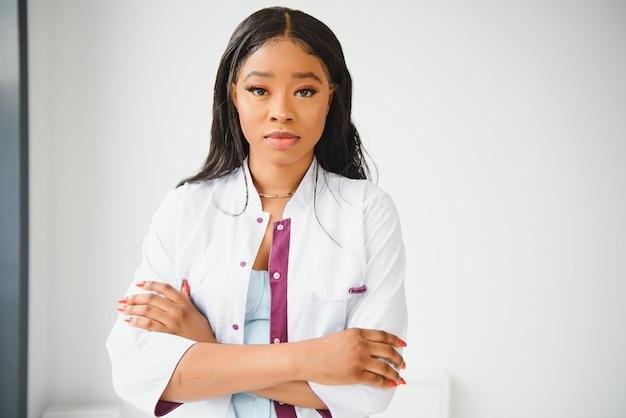 Portret van mooie glimlachende vrouwelijke afro-amerikaanse arts die in een medisch kantoor staat. gezondheidszorgconcept, medische verzekering, kopieerruimte.