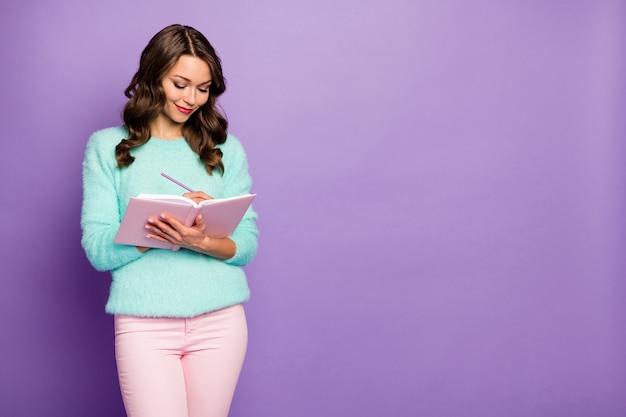 Portret van mooie golvende dame hold planner schrijf essay verantwoordelijke student hoofdcitaten schrijven beroemde schrijvers dragen pastel fuzzy sweater roze broek.