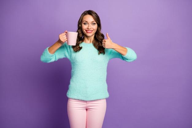 Portret van mooie grappige krullende dame houd warme koffie drank beker duim omhoog vinger omhoog goedkeuren van goede smaak van drank dragen fuzzy pastel trui roze broek.