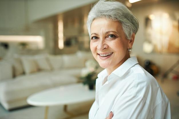 Portret van mooie grijze haired rijpe onderneemster in wit overhemdszitting bij hotellobby