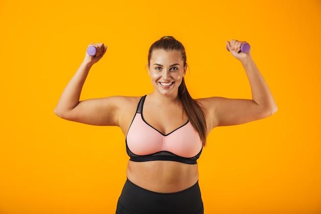 Portret van mooie grote sportvrouw in sportieve beha opheffing halters, geïsoleerd op gele achtergrond
