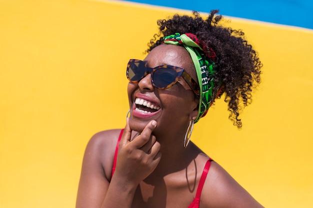 Portret van mooie handen van de afro amerikaanse vrouw op gezicht terwijl het glimlachen