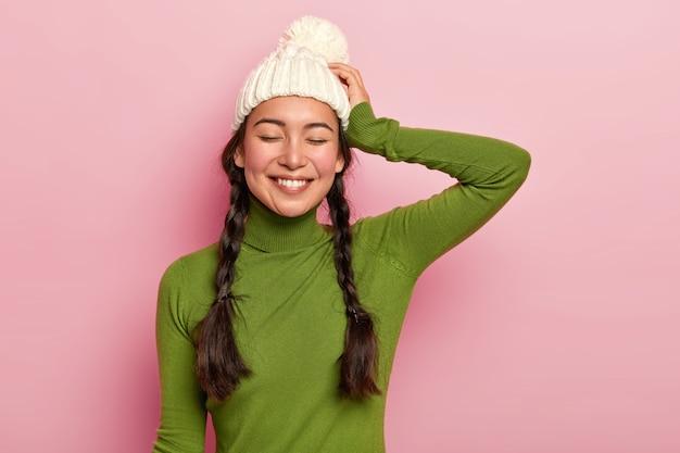Portret van mooie hipster meisje, houdt de ogen dicht, gekleed in groene poloneck en hoed, tevreden na vrije tijd doorbrengen met naaste persoon herinnert zich aangenaam moment tijdens romantische date